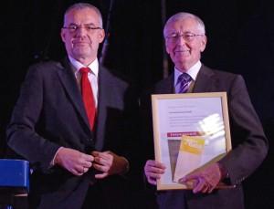 Der Präsident des Schwäbischen Chorverbands, Dr. Jörg Schmidt (links), hatte die Ehrenurkunde sowie einen Scheck dabei. Foto: Krytzner